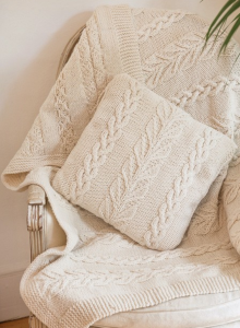 Cream colored cable and leaf knit cushion cover