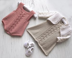 Old pink knit baby romper with heart buttons on shoulder straps and delicate leaf pattern running down the front