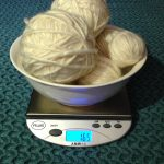 Cream colored mystery yarn balls in a bowl on a digital scale
